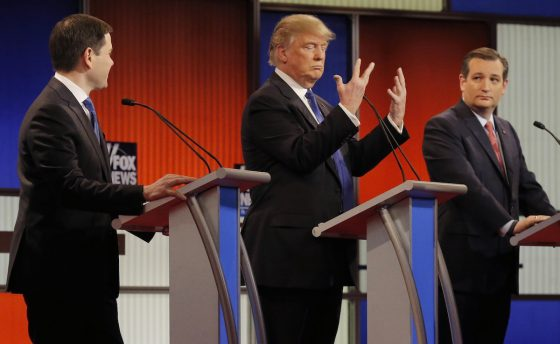 Donald Trump shows off the size of his hands as rivals Marco Rubio and Ted Cruz look on at the start of the Republican presidential candidates debate in Detroit, Michigan, March 3, 2016. REUTERS/Jim Young